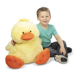 Boy sitting next to jumbo ducky stuffed animal
