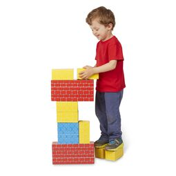 Boy stacking colorful jumbo cardboard blocks