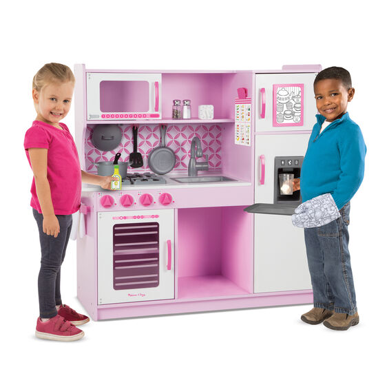Boy and girl playing at pink pretend kitchen