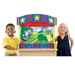 Boy and girl performing puppet show with tabletop theater