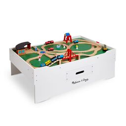 Activity table topped with toy train tracks and trains