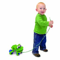 By pulling green wooden frog with blue wheels
