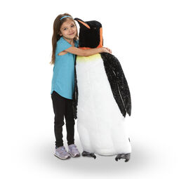 Girl hugging large penguin stuffed animal